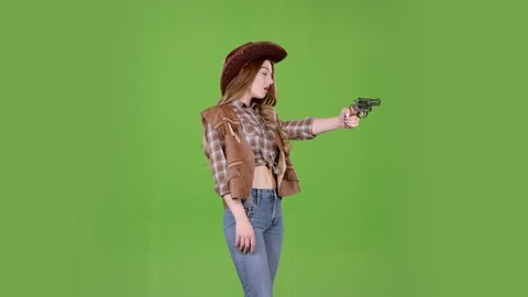 Girl in a hat, cowboy boots and a vest shoots a revolver. Green screen