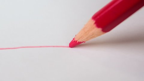 Drawing red line on white drawing paper with red color pencil. artistic concept.