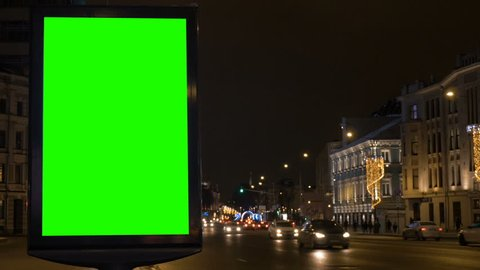 A billboard with a green screen on a busy festive street.