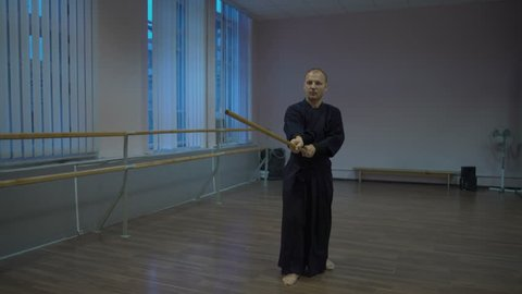 Exercise with the Kendo Master's Wooden Sword in the Blue Kimono Early In the morning in the Sports Hall