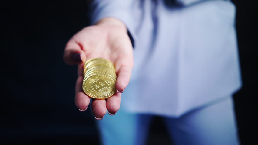 Fashion woman in business suit holding golden coin bitcoin in hand, blured portrait smiling woman | Shutterstock HD Video #1007274772
