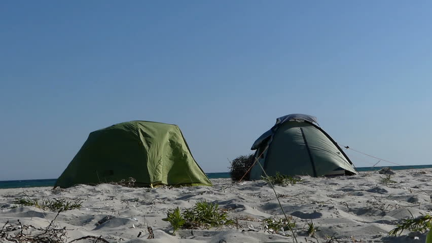 Two tents are on a sandy beach of the Black Sea at sunset - HD stock & Two Tents Under Bursts Of Wind On A Sandy Seacoast In Slo-mo Stock ...
