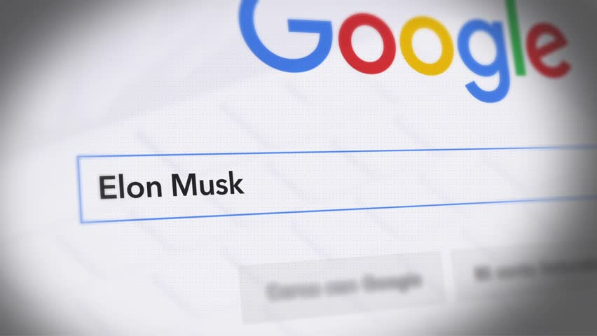 USA-Popular searches in 2018 Google Search Engine - Search For Elon Musk -  Monitor with reflection hands typing a search on google