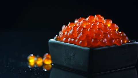 Red Caviar in rotated over black background. Close-up salmon caviar rotation. Delicatessen. Gourmet food. Texture of caviar. Seafood. 4K UHD video
