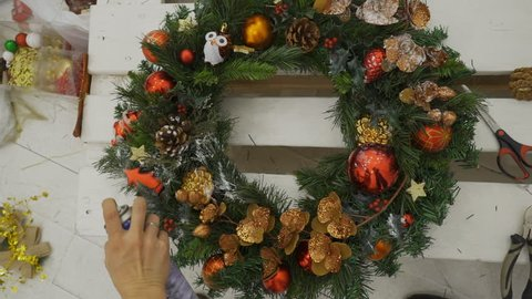Close up of Chirstmas wreath is being painted in studio. Female designer is spreading white color to green branches to make an effect of snow and create the atmosphere of holliday for celebration. The