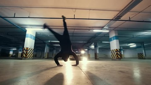 Young stylish guy freerunner doing a flip from the wall in the garage, parkour acrobatic elements, slow motion