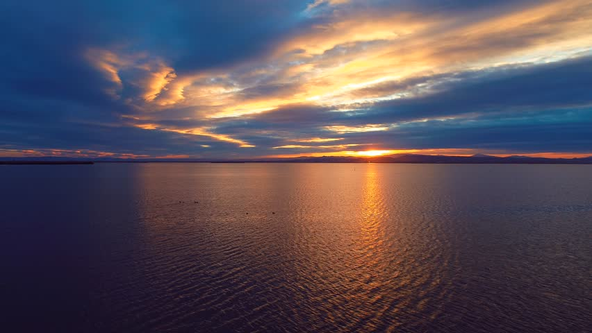 17 Aerial 4k cinematic slow motion . Sun disk ahead, hide behind dense stripe of clouds, move down to horizon line. Sun reflexion on flat water delta and birds flying