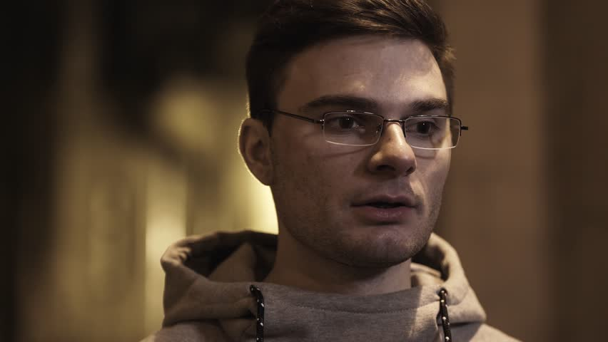 Portrait of young cauasian unshaved guy in glasses and gray hoodie out of breath turns around in backstreet at night | Shutterstock HD Video #1007385652