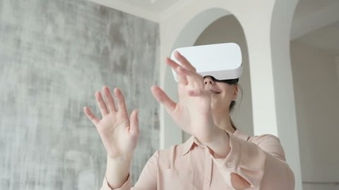 Happy cute teen girl using 3D virtual reality headset. Virtual reality game. Girl with pleasure uses head-mounted display. Woman wearing VR headset in living room