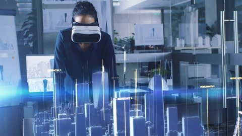 Professional Female Architect Wearing Makes Gestures with Augmented Reality Headset, Shows Statistics for 3D City Model. High Tech Office Use Virtual Reality Modeling Software Application.