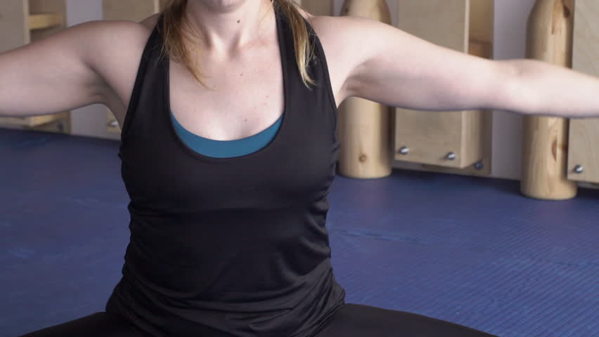 Close-up of woman's torso on the floor folds her hands in a lotus pose. Woman slowly performs exercise for flexibility of muscles and achievement of peace and tranquility.