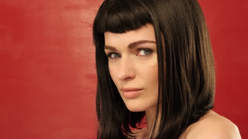 brunette woman with bob hair looking at camera on red background