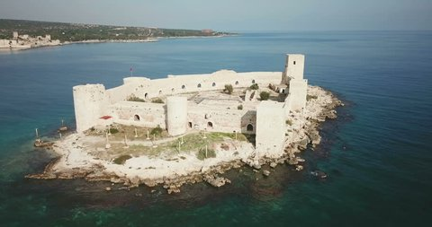 Aerial drone view low pan left around point of interest Kizkalesi Castle island ocean to reveal mainland coastline visible in background in Mersin, Turkey. 4K at 23.97fps. Part 2 of 2 360 degrees