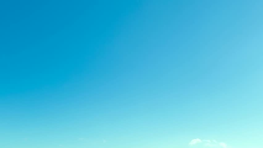 Puffy fluffy white clouds blue sky time lapse motion background. Cumulus clouds form against a dark blue sky. Timelapse of white clouds with blue sky. 4K.