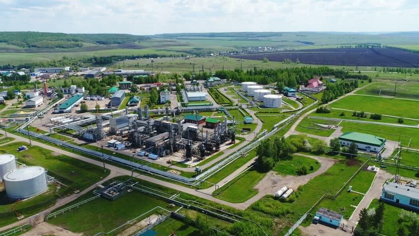 upper view fuel processing factory territory with industrial buildings surrounded by pipes against rural scenery
