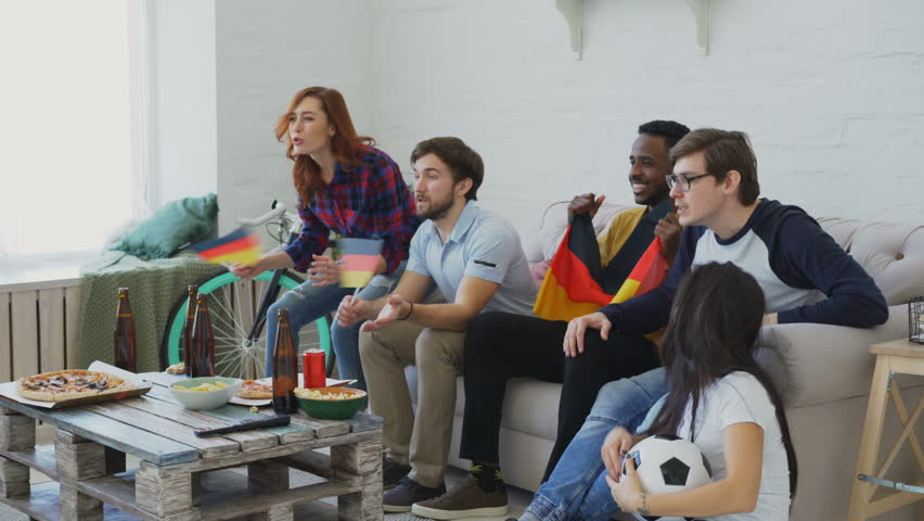 Multi-ethnic group of friends sports fans with German flags watching football championship on TV together at home and cheering up favourite team | Shutterstock HD Video #1007483452