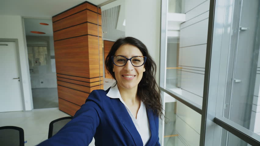 POV of young businesswoman in suit having online video chat using smartphone camera and talking to his colleagues in modern office