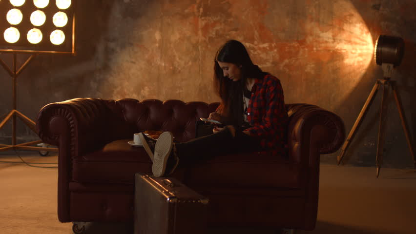 Gorgeous brunette hipster woman in stylish outfit browsing social networks on smart phone while sitting comfortably on the couch in dimmed lighting in loft home interior. | Shutterstock HD Video #1007495602