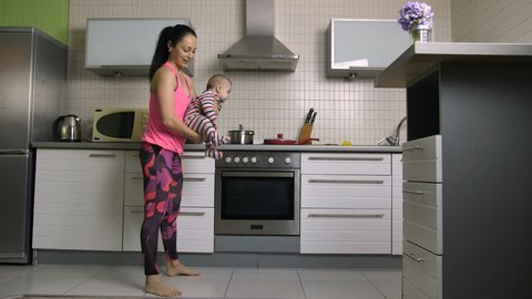 Smiling beautiful mixed race woman doing backward lunges with baby in hands. Young attractive housewife doing reverse lunges exercises during workout in the kitchen holding infant child. Dolly shot.