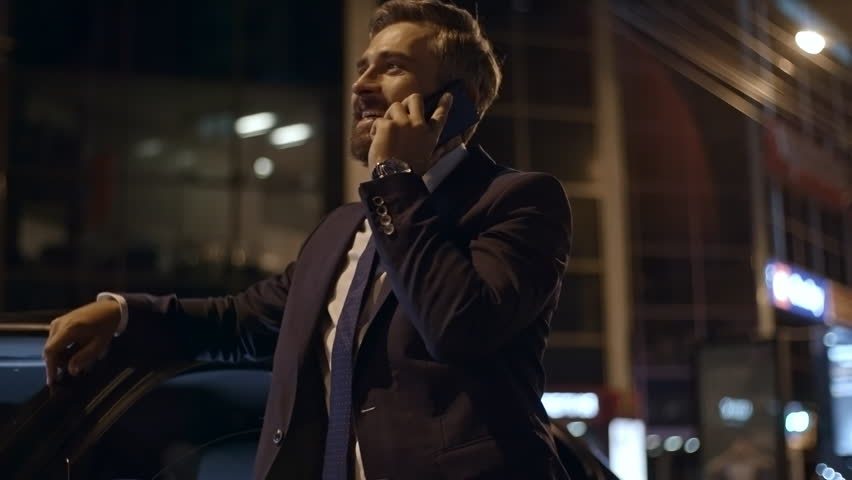 PAN with low angle of bearded businessman in suit standing before car outdoors at night and chatting on mobile phone | Shutterstock HD Video #1007538232