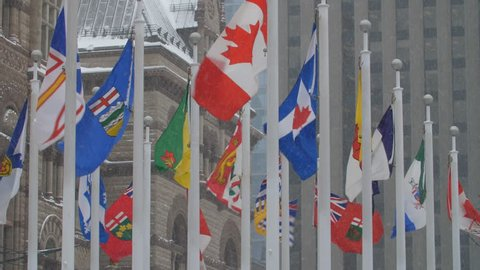 Flags of Canada and Canadian provinces. Snow falling. Old City Hall, Toronto.