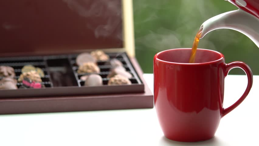Cup of Hot Coffee or Tea. Cup of hot beverage with Steam. Assorted chocolate box tasty dessert.  | Shutterstock HD Video #1007562862