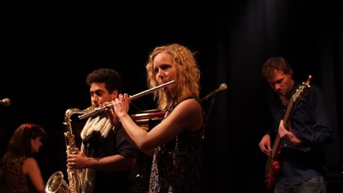 Flutist, saxophone player, pianist and bass player performing live.