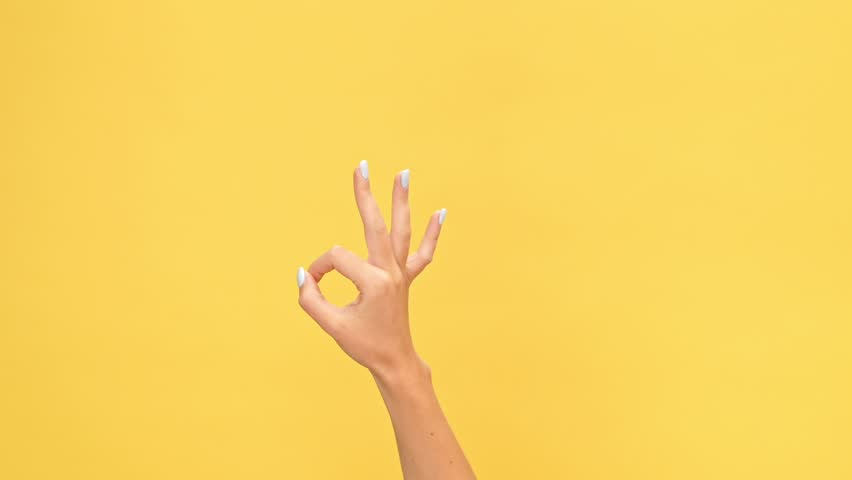 Woman hand showing ok gesture over yellow background | Shutterstock HD Video #1007574922