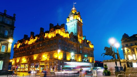 Edinburgh, UK. Night view of Edinburgh, Scotland with illuminated Balmoral Hotel and clock tower. Time-lapse of car traffic trail lights with blue sky