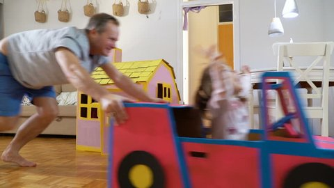 Funny little girl and her father are driving handmade cardboard car. Father and daughter playing in living room together.