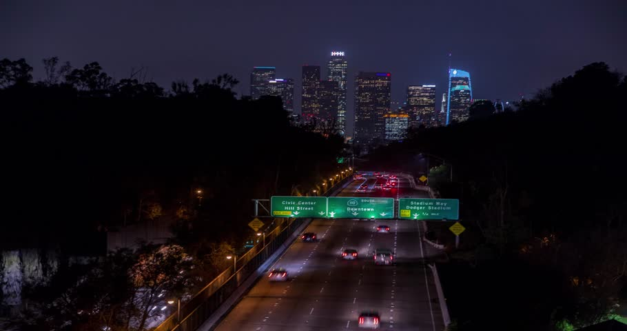 Beautiful view of Los Angeles Skyline from 110 Freeway at dusk. Close up. Traffic passing by. Timelapse with zoom effect. California, United States. | Shutterstock HD Video #1007616052