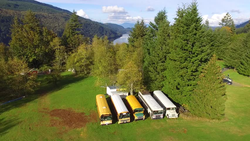 Rising drone shot of an North American countryside beside a tranquil lake, visiting school buses | Shutterstock HD Video #1007641627