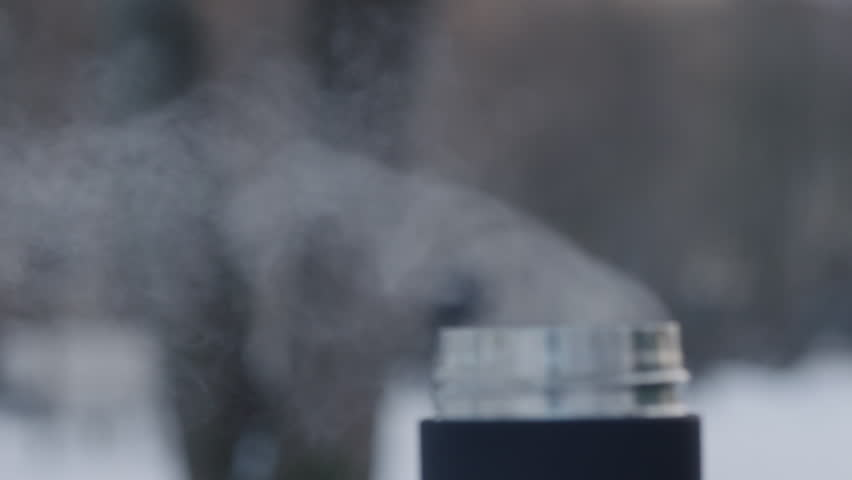 Slow motion handheld shot of steam rising from the thermo mug