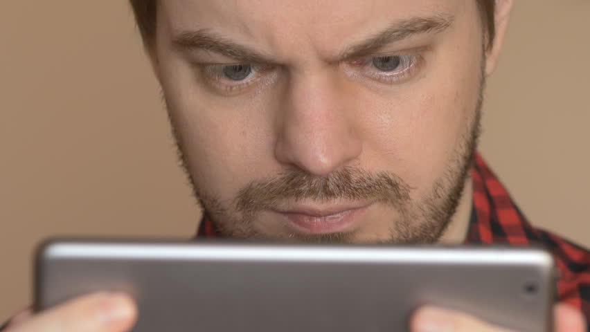Young man using tablet computer touchscreen in home. | Shutterstock HD Video #1007663572