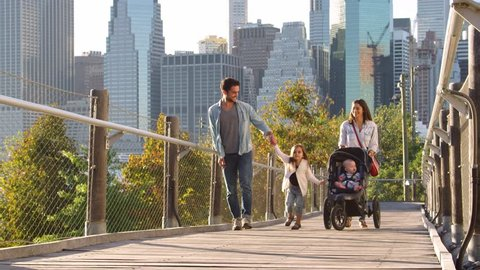 Young family walking with stroller on footbridge, Manhattan