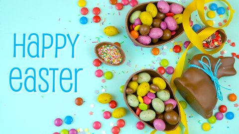 Happy Easter decadent chocolate background overhead with Easter eggs and candy on a rustic wood background animated text.