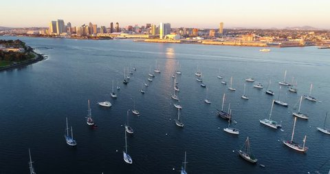 Aerial Drone video with boats moored at Coronado in the foreground and view of the Downtown San Diego in the background during Sunset. San Diego, California.