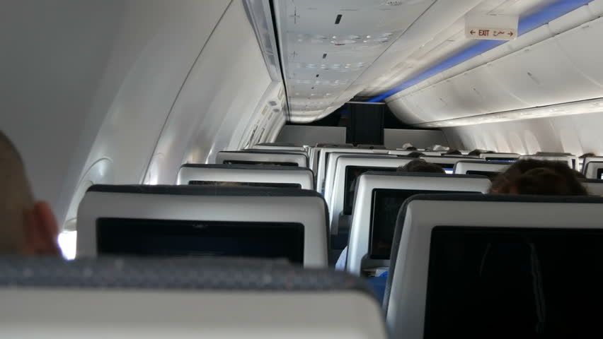 Passengers in comfortable seats of aircraft with the screens in chairs   Shutterstock HD Video #1007712676
