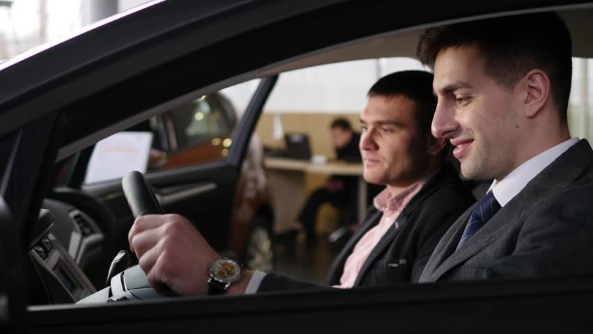 Car dealer gives the customer the car keys in car   Shutterstock HD Video #1007713798