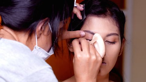 Asian woman makeup her face at studio. Specialist doing makeup for model.