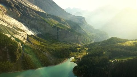 Aerial view of a beautiful mountain lake and landscape bathed in evening light in Switzerland