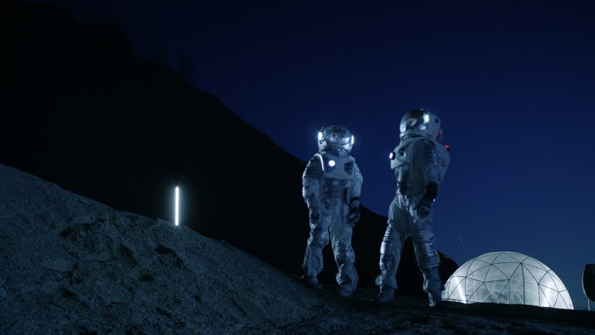Two Astronauts in Space Suits Stand on the Alien Planet Looking at the Sky. In the Background Base with Geodesic Dome. Other Worlds Colonization and Space Travel Concept. Shot on RED EPIC-W 8K Camera. | Shutterstock HD Video #1007756872