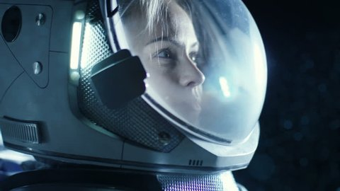 Portrait Shot of the Courageous Female Astronaut Wearing Helmet in Space, Looking around in Wonder. Space Travel, Exploration and Solar System Colonization Concept. Shot on RED EPIC-W 8K Helium Cinema