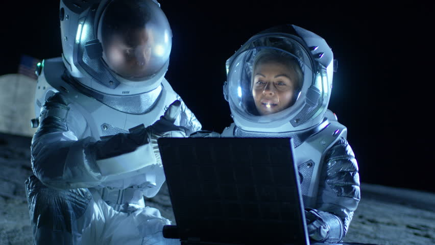 Two Astronauts Wearing Space Suits Work on a Laptop, Exploring Newly Discovered Planet, Communicating with the Earth. Space Travel, Exploration and Colonization Concept. Shot on RED EPIC-W 8K Camera.
