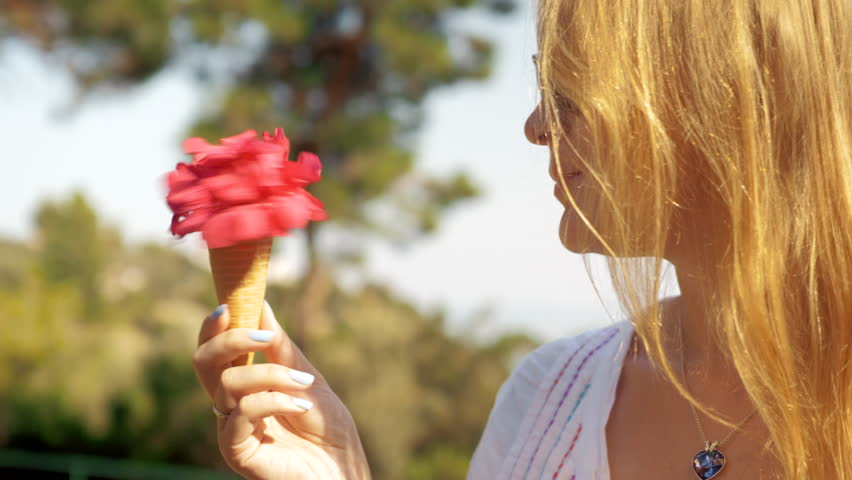 Loop shot of coquettish blond girl in sunglasses spinning in hand a red flower  bouquet  in waffle cone. Summer scene