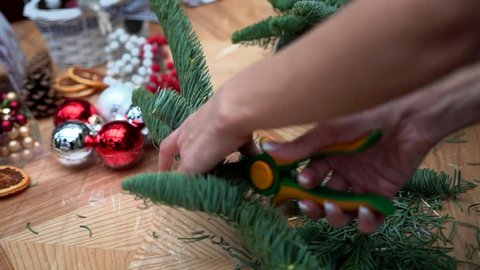 Female hands prepare fir-tree branches for a handcrafted christmas table centerpiece arrangement: a basket with floral foam, faux berries, cotton balls, candles and ribbons, close-up.
