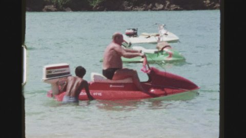 PATTAYA, THAILAND, MAY 1978. Native Man Starting The Outboard Engine Of A Red Jetski With A Male Caucasian Tourist Riding It By A Beachshore.