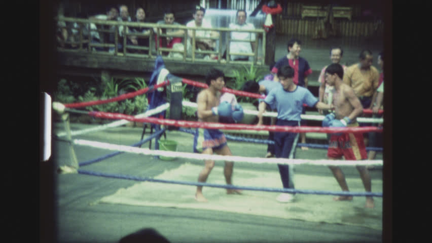 Two Muay Thai Kickboxers Fighting Each Other With Hard And Fast Leg Kicks  Until One Hits The Ground, At The Cultural Village Show.