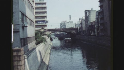 TOKYO, JAPAN, MARCH 1978. Ginza City Impression Of River Channel Between Buildings With Freight Boats And A Train Passing Over A Bridge
