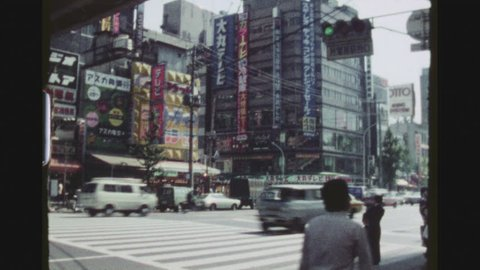 TOKYO, JAPAN, MARCH 1978. Ginza, Chuo Ko Prefecture. Pan Over Busy Shopping Street With Traffic